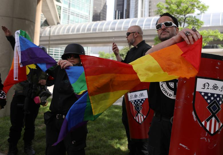 Members of the National Socialist Movement, a white nationalist group, tear apart a pride flag as they demonstrate against Motor City Pride in Detroit. REUTERS/Jim Urquhart