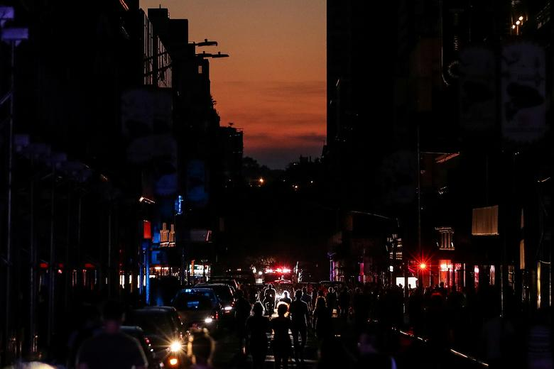 People walk along a dark street near Times Square area, as a blackout affects buildings and traffic during widespread power outages in Manhattan, New York, July 13, 2019. A wide swath of New York s Manhattan borough was plunged into darkness Saturday after a transformer explosion knocked out power to subways, stores and Broadway theaters, but the city s main utility said it had restored most power within hours. REUTERS/Jeenah Moon