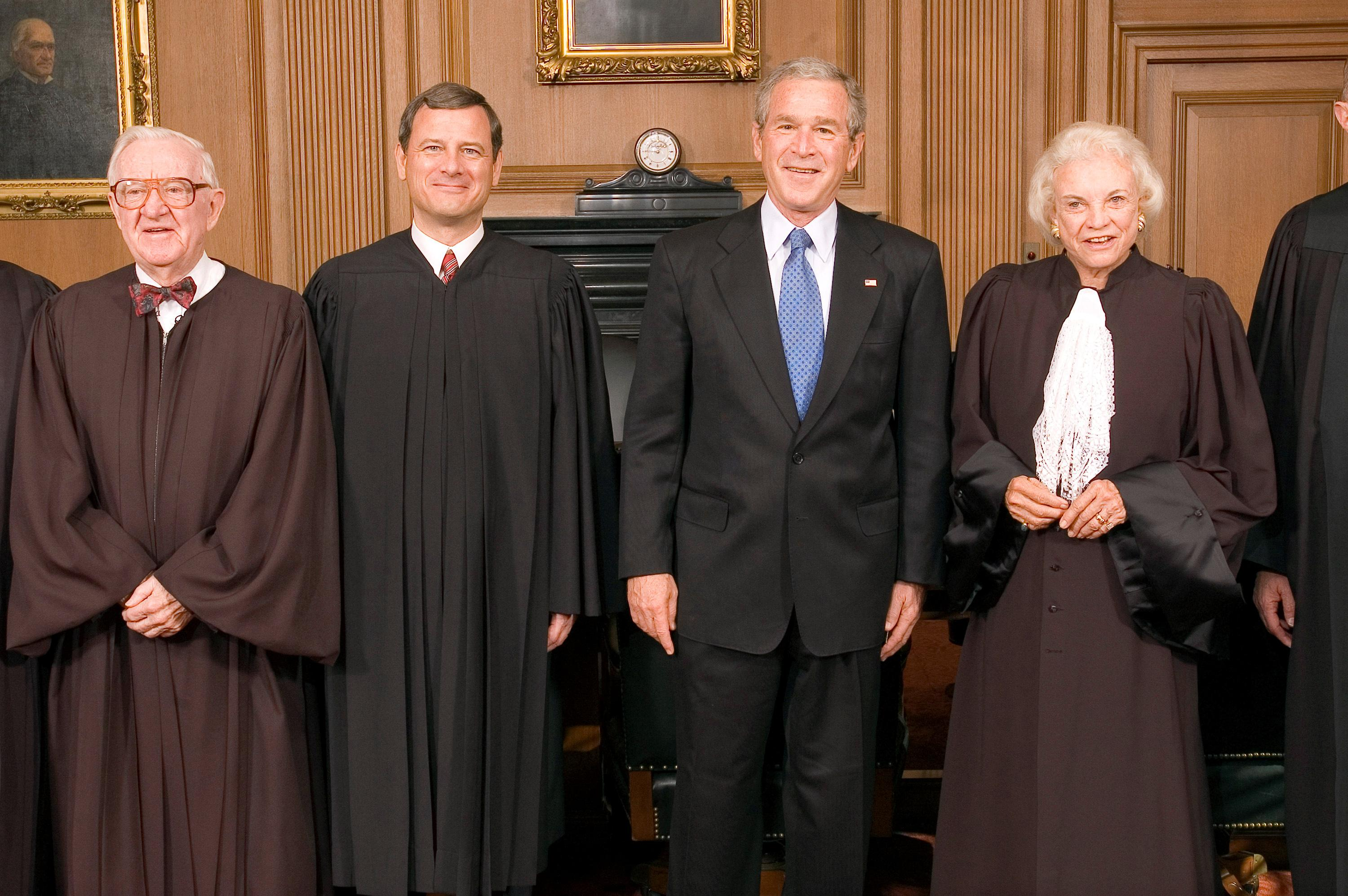 U.S. Chief Justice John Roberts (2nd L) poses for pictures with President George W. Bush (2nd R) and senior Justices John Paul Stevens (L) and Sandra Day O'Connor in the Chief Justice's Conference Room at the Supreme Court in Washington, D.C. October 3, 2005. Ken Heinen/Pool