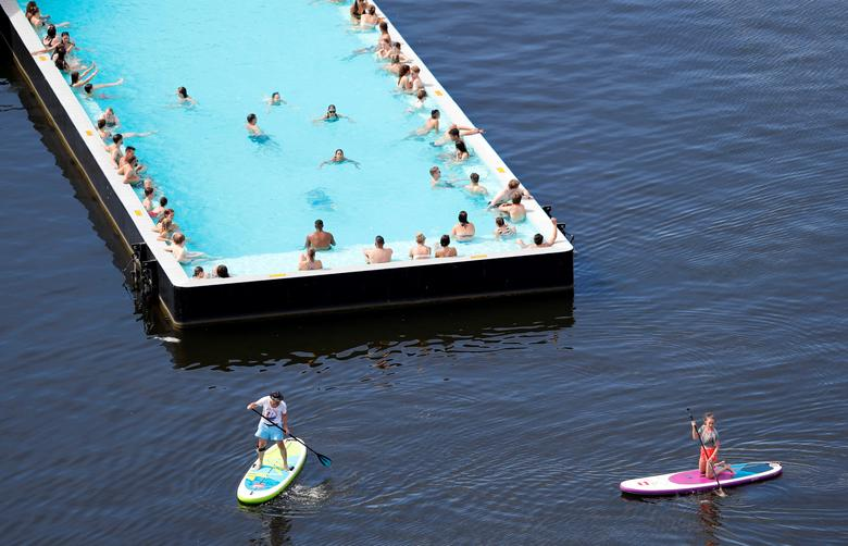 People cool off in the futuristically designed 'Badeschiff' on the Spree river as temperatures reach new record highs in Berlin, Germany. REUTERS/Fabrizio Bensch