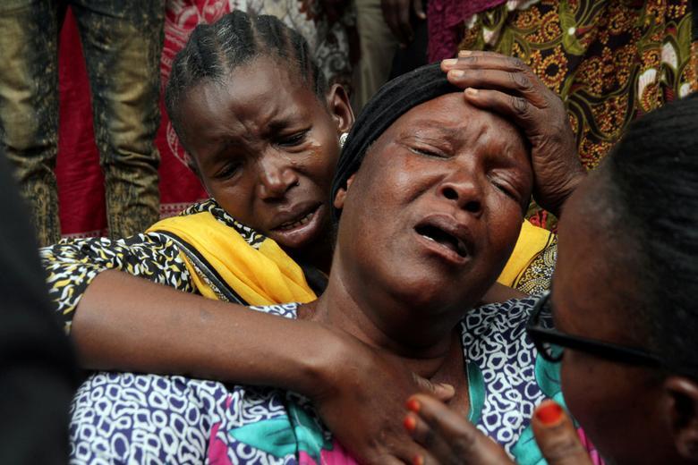 Akrabalar ölü akrabalarını Morogoro sevkhanesinin dışına yasladılar; bir yakıt tankeri patladıktan sonra, Tanzanya'nın doğusundaki Morogoro'da bulunan su birikintilerindeki su birikintilerinden sıvı toplayan bir insan kalabalığı öldürdü.  REUTERS / Emmanuel Herman