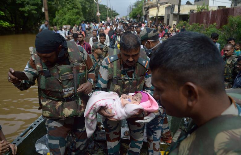 Bir ordu askeri, selden etkilenen insanları Hindistan'ın batısında bulunan Maharashtra'nın batı eyaletindeki Sangli bölgesinde daha güvenli bir yere tahliye ederken bir bebek taşıyor.  REUTERS / Stringer