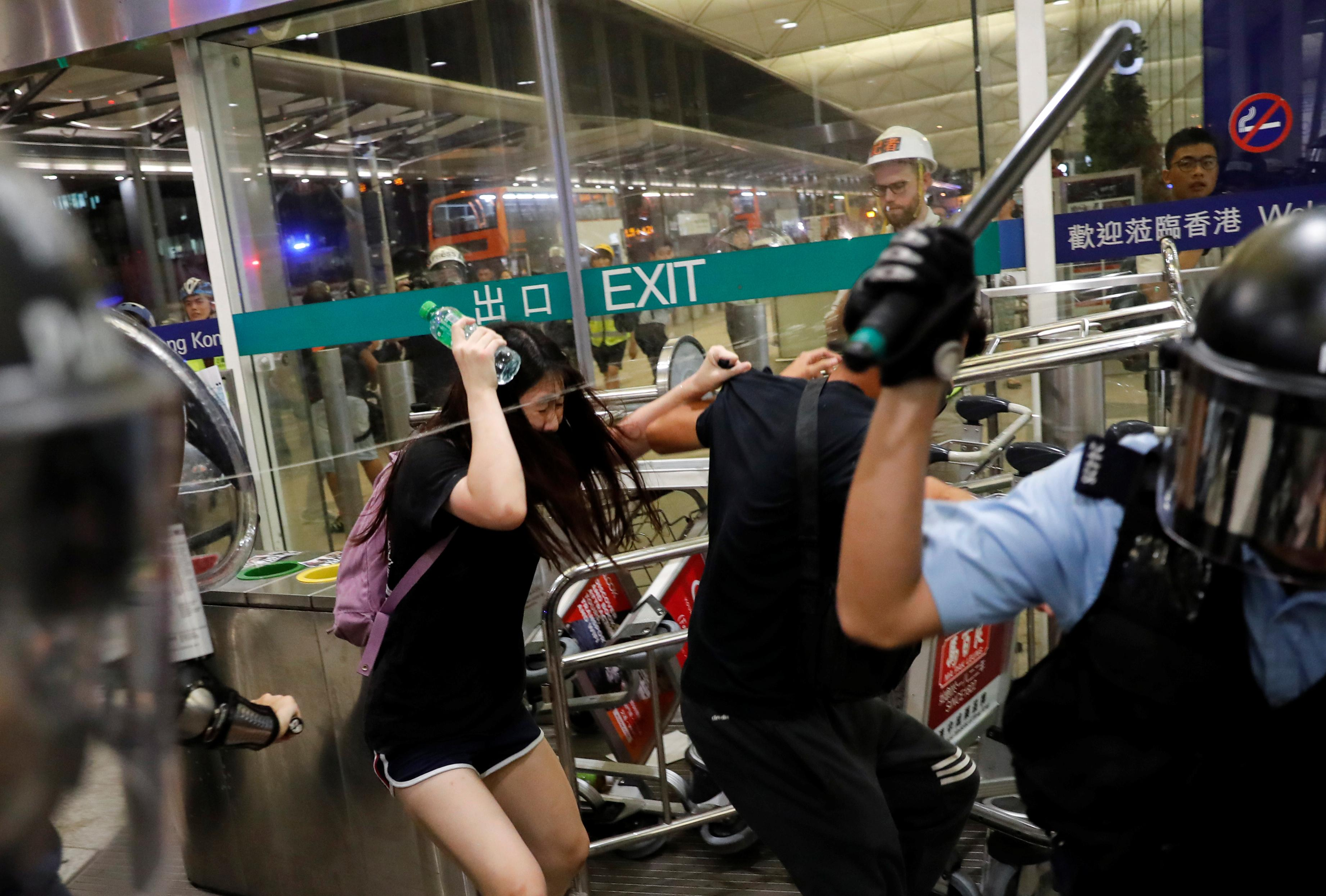 Police, protesters clash at Hong Kong airport after flights halted for second day
