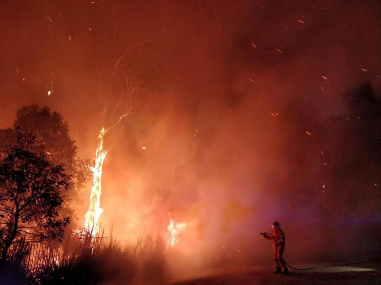 Firefighters battling a bushfire in Peregian Springs on the Sunshine Coast, Australia. AAP Image/John Park/via REUTERS