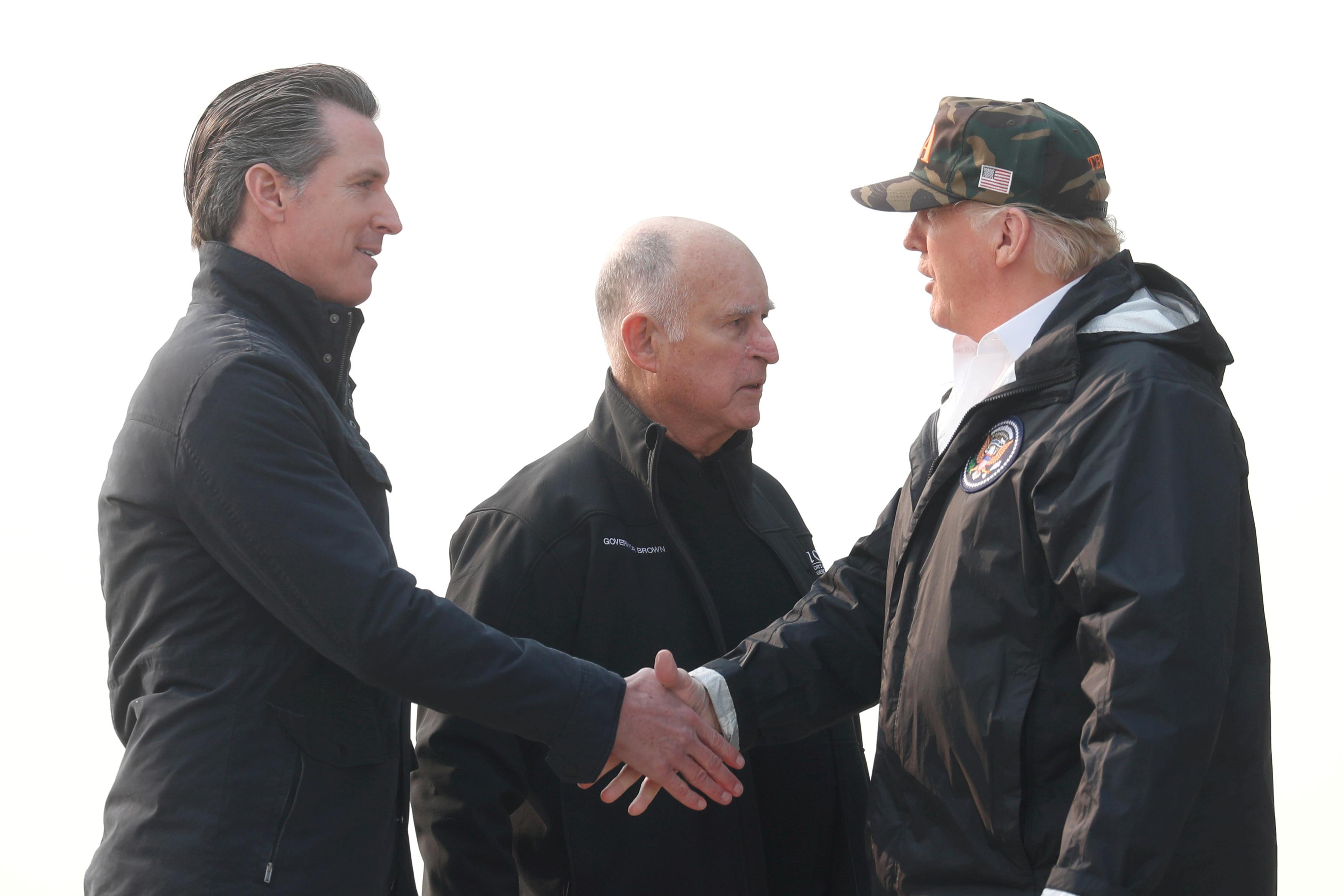U.S. President Donald Trump shakes hands with California's then-Governor-elect Gavin Newsom (L) after greeting then-Governor Jerry Brown (C) upon arriving at Beale Air Force Base, California, U.S., November 17, 2018. Leah Millis