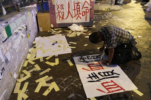 Lou Tit-Man, 73, writes a protest sign outside Mong Kok police station in Hong Kong, China September 23, 2019. The sign reads ''blood for blood''. REUTERS/Tyrone Siu