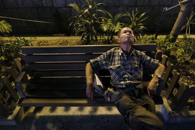 Lou Tit-Man, 73, takes a nap in a park in Hong Kong, China September 23, 2019.  REUTERS/Tyrone Siu