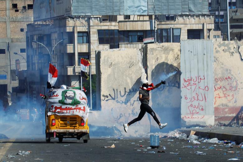Bir gösterici, 1 Kasım'da Bağdat'taki hükümet karşıtı protestolar sırasında göz yaşartıcı gaz tüpünü attı. REUTERS / Khalid Al Mousily