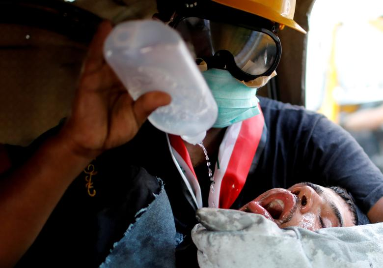 Iraklı bir gösterici, 1 Kasım'da Bağdat'ta devam eden hükümet karşıtı protestolar sırasında göz yaşartıcı gazdan etkilendikten sonra tıbbi yardım aldı. REUTERS / Thaier Al-Sudani