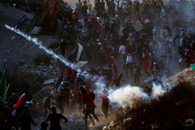 Göstericiler, 1 Kasım'da Bağdat'taki hükümet karşıtı protestolar sırasında göz yaşartıcı gaz tüpü koymaya çalışıyorlar. REUTERS / Thaier Al-Sudani
