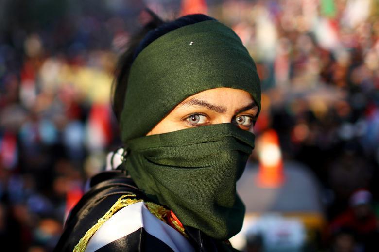 Iraklı bir kadın gösterici, 1 Kasım'da Bağdat'ta devam eden hükümet karşıtı protestolara katılıyor. On binlerce Iraklı, kitlesel hükümet karşıtı gösterilerin en büyük gününde siyasi seçkinlerin kök-dal çöküşünü talep eden Cuma günü Bağdat merkezini vurdu. Saddam Hüseyin'in düşmesinden beri.  REUTERS / Ahmed Jadallah