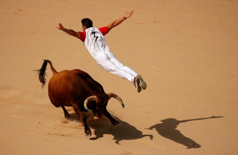 A recortador jumps over a bull during a contest in a bullring at the San Fermin festival in Pamplona, Spain, July 13, 2019. REUTERS/Jon Nazca