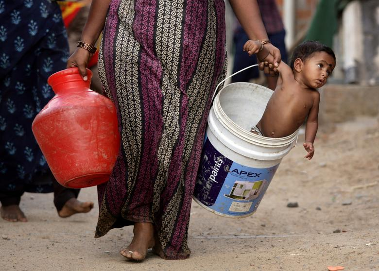 A woman carries her son in a bucket after collecting water from a municipal water tanker on the outskirts of Chennai, India, July 4, 2019. REUTERS/P. Ravikumar
