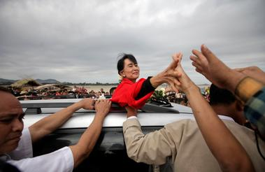 FILE PHOTO: Myanmar pro-democracy leader Suu Kyi shakes hands with...