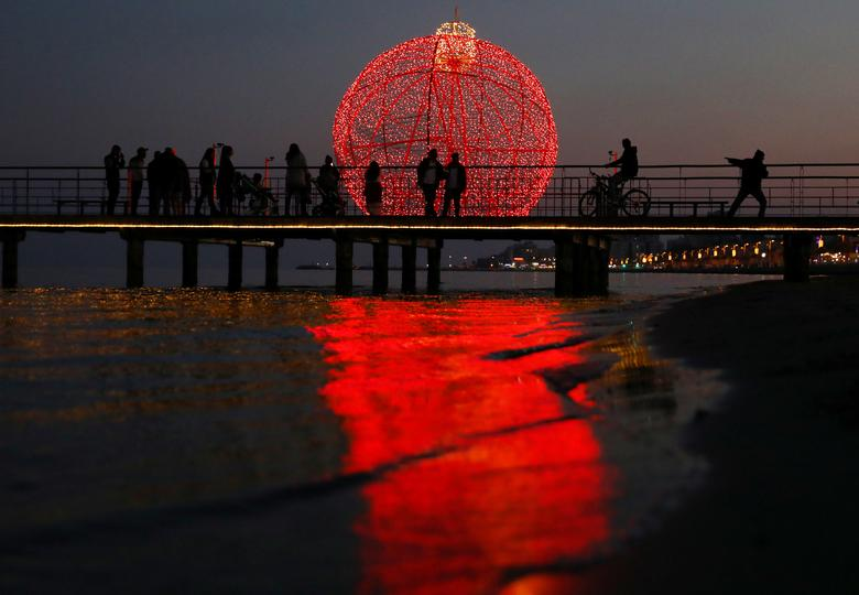 Se ve a las personas en un muelle frente a una gigantesca bola de Navidad iluminada en Larnaca, Chipre, 22 de diciembre de 2019. REUTERS / Yiannis Kourtoglou