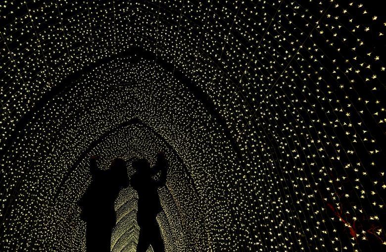 Los visitantes posan en una instalación luminosa cuando el sendero iluminado se abre en Kew Gardens en el oeste de Londres, Gran Bretaña, el 19 de noviembre de 2019. REUTERS / Toby Melville