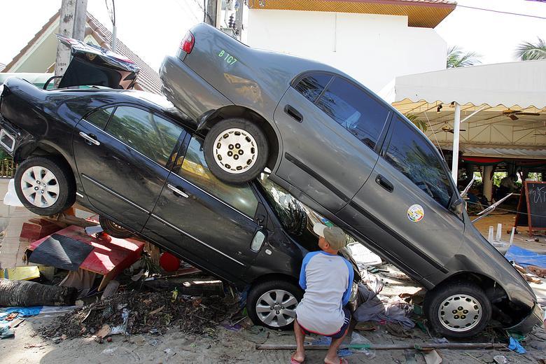 Un hombre tailandés mira un automóvil destrozado después de que un maremoto golpeó la playa de Pathong, cerca de Phuket, el 27 de diciembre de 2004. REUTERS / Luis Enrique Ascui
