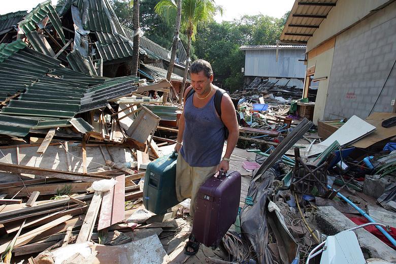Michael Will de Inglaterra camina entre las ruinas de su hotel aplastado después de regresar por su equipaje, después de la devastación causada por las mareas en la playa de Pathong, cerca de Phuket, Tailandia, 27 de diciembre de 2004. REUTERS / Luis Enrique Ascui