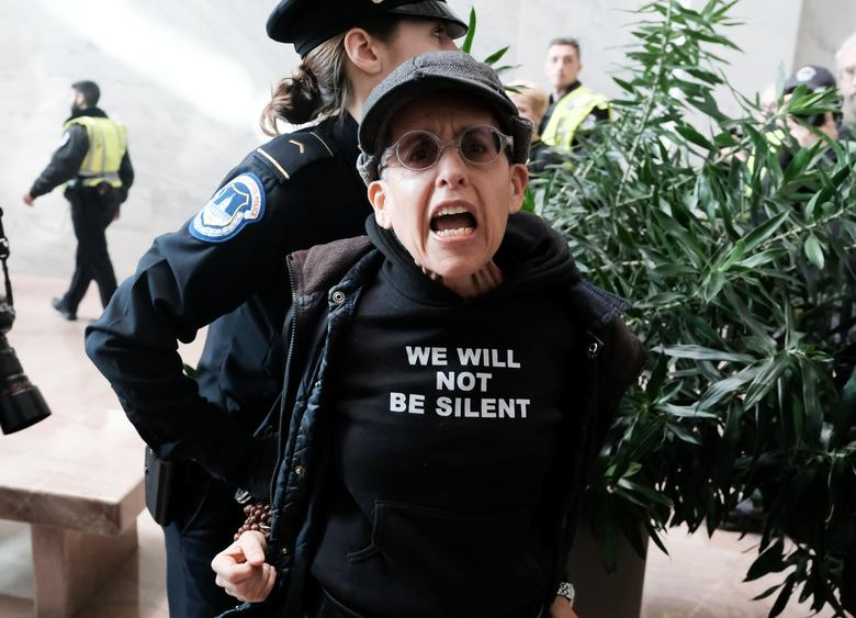 Police detain a protester during a demonstration calling for the removal of President Donald Trump inside of the Hart Senate Office Building, on Capitol Hill in Washington, January 16, 2020. REUTERS/Michael A. McCoy