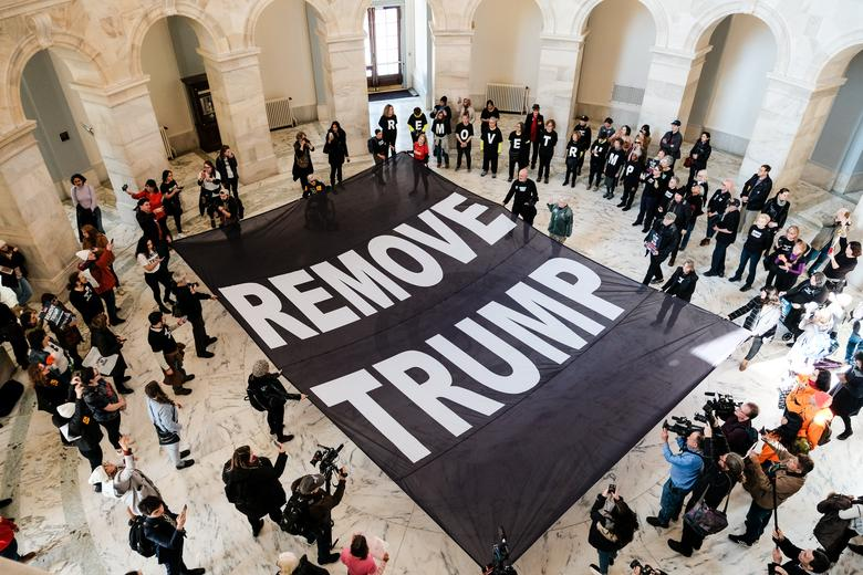 Protestors lay a banner calling for the removal of President Donald Trump inside of the Russell Senate Office Building during a demonstration on Capitol Hill in Washington, January 16, 2020. REUTERS/Michael A. McCoy
