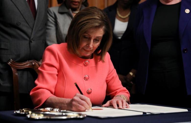 House Speaker Nancy Pelosi (D-CA) signs the two articles of impeachment of President Donald Trump before sending them over to the Senate during an engrossment ceremony at the Capitol in Washington, January 15, 2020. REUTERS/Leah Millis