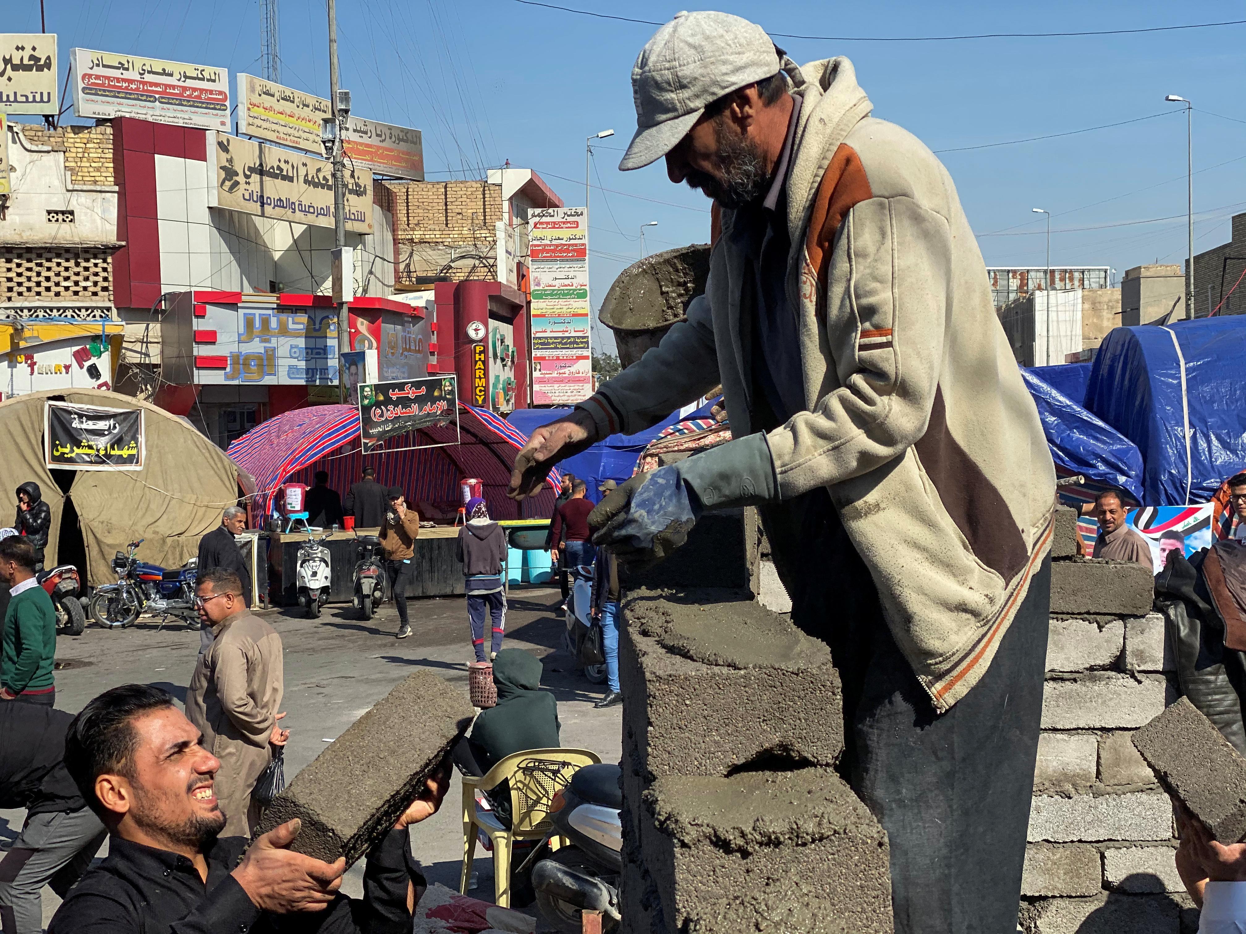 Iraqis rebuild wrecked protest camp as violence escalates