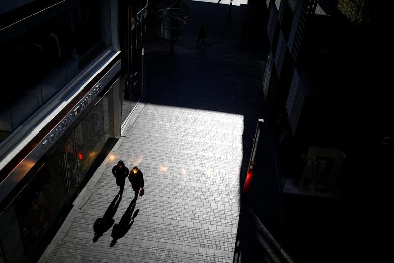 People wearing face masks walk at a shopping mall in Beijing, China, February 4. REUTERS/Carlos Garcia