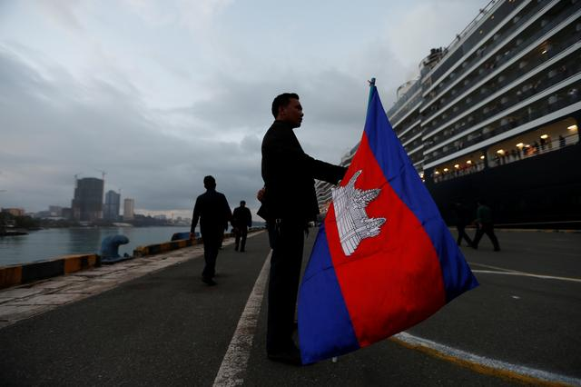 A man holds a Camboadian flag as MS Westerdam, a cruise ship that spent two weeks at sea after being turned away by five countries over fears that someone aboard might have the coronavirus, docks in Sihanoukville, Cambodia February 14, 2020.  REUTERS/Soe Zeya Tun
