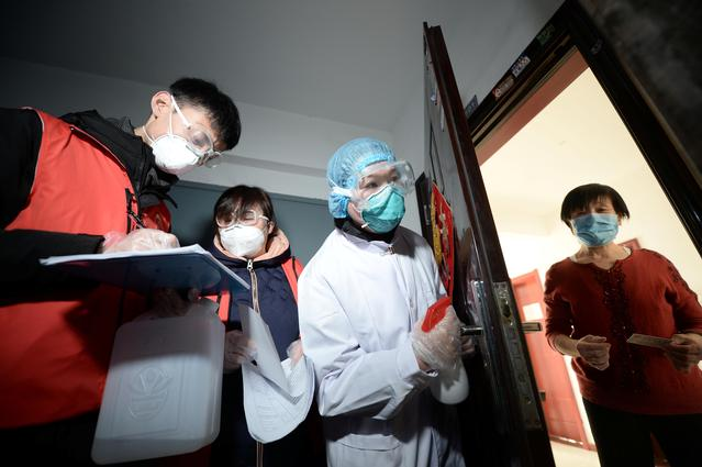 Community workers and medical staff visit a woman at her home as they conduct door-to-door search to inspect residents following an outbreak of the novel coronavirus in the country, in Tianjin, China February 12, 2020.  China Daily via REUTERS
