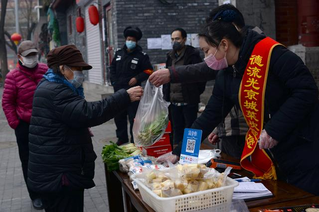 A woman wearing a face mask buys vegetables from a stall set up by a restaurant outside its outlet in central Beijing, following an outbreak of the novel coronavirus in China, February 13, 2020. REUTERS/Tingshu Wang