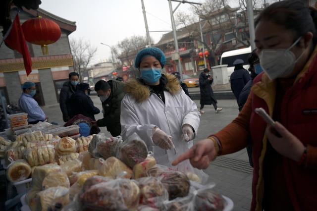 A woman wearing a face mask buys food from a stall set up by a restaurant in central Beijing, following an outbreak of the novel coronavirus in China,  February 13, 2020. REUTERS/Tingshu Wang