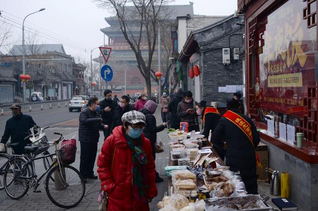 People wearing face masks buy food from a stall set up by a restaurant outside its outlet in central Beijing, following an outbreak of the novel coronavirus in China, February 13, 2020. REUTERS/Tingshu Wang