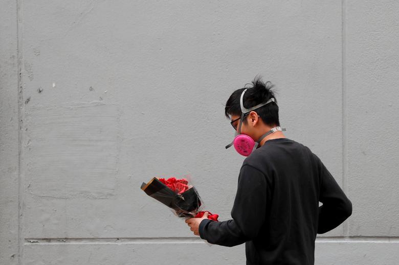 Un hombre usa una máscara de gas mientras sostiene un ramo de flores el día de San Valentín en Hong Kong.  REUTERS / Tyrone Siu
