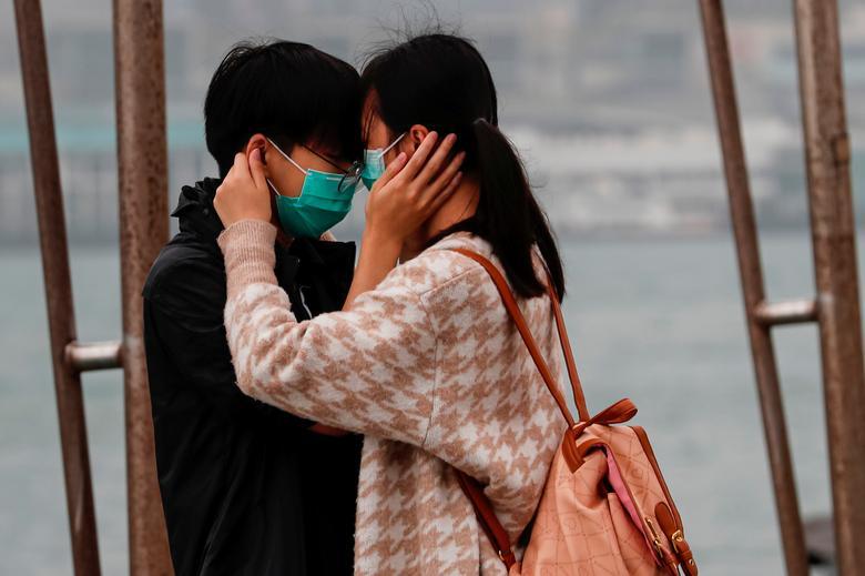 Una pareja usa máscaras como el abrazo en el Día de San Valentín en Hong Kong.  REUTERS / Tyrone Siu