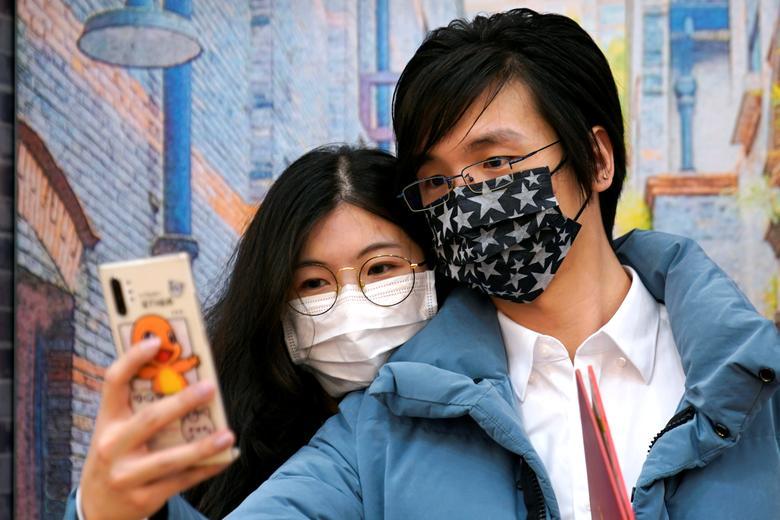 Wang, de 32 años, y su esposa Shi, de 30, con máscaras son vistos en una oficina de registro de matrimonios en el día de San Valentín en Shanghai, China.  REUTERS / Aly Song