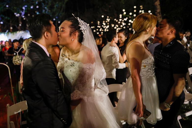 Las parejas del mismo sexo se besan durante un intercambio ceremonial de votos en un país donde el matrimonio entre personas del mismo sexo sigue siendo ilegal, en el Día de San Valentín, en la ciudad de Quezon, Metro Manila, Filipinas.  REUTERS / Eloisa Lopez