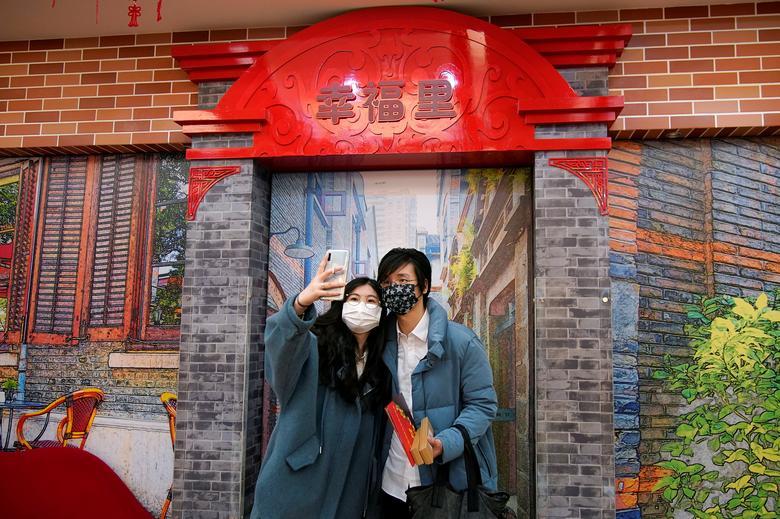 Wang, de 32 años, y su esposa Shi, de 30, posan para una selfie mientras Wang sostiene sus certificados de matrimonio en una oficina de registro de matrimonios en el Día de San Valentín en Shanghai, China.  REUTERS / Aly Song
