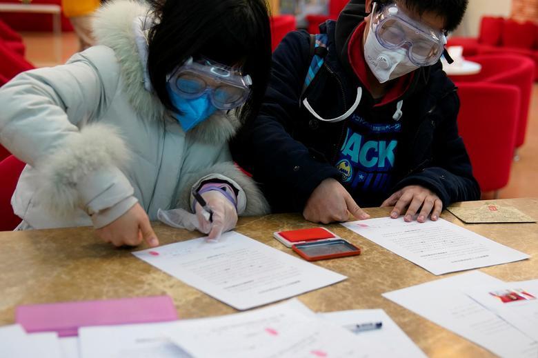 Jia, de 29 años, y su esposa Su, de 28 años, con máscaras toman la impresión de las huellas digitales en una sesión de registro en una oficina de registro de matrimonios en el Día de San Valentín en Shanghai, China.  REUTERS / Aly Song