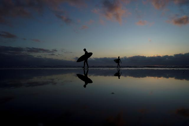 FILE PHOTO: A father and his son make their way in from surfing at Cardiff State Beach in Encinitas, California, U.S. October 17, 2019.    REUTERS/Mike Blake/