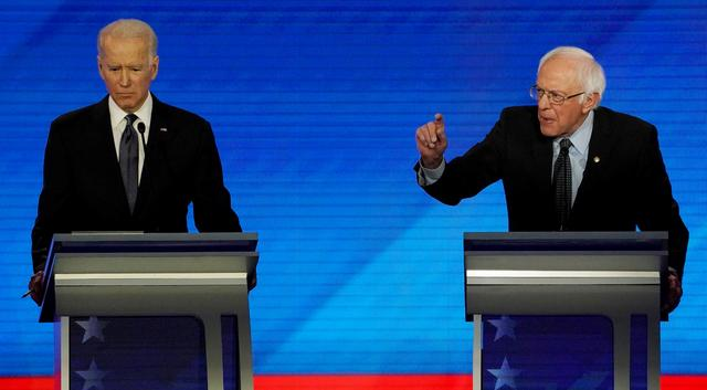 FILE PHOTO: Senator Bernie Sanders (I-VT) (R) makes a point next to former Vice President Joe Biden during the eighth Democratic 2020 presidential debate at Saint Anselm College in Manchester, New Hampshire, U.S., February 7, 2020. REUTERS/Brian Snyder/File Photo