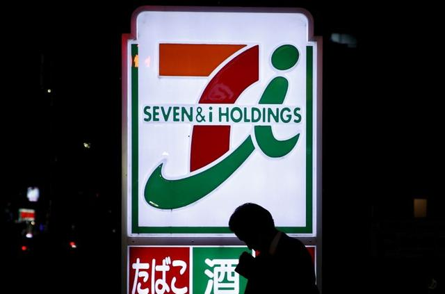 A pedestrian walks in front of a signage of Seven & I Holdings' 7-Eleven convenience store in Tokyo, Japan, in this April 7, 2016 file photo.