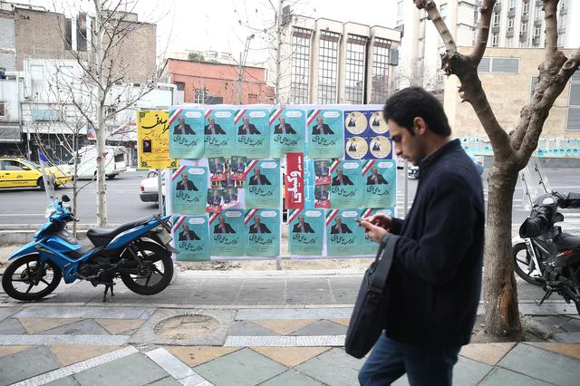 A man walks past parliamentary election campaign posters in Tehran, Iran February 19, 2020. Picture taken February 19, 2020. WANA (West Asia News Agency)/Nazanin Tabatabaee via REUTERS