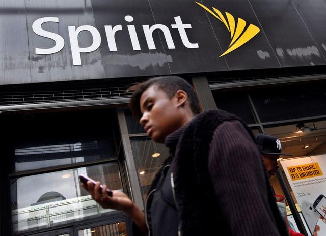 FILE PHOTO: A woman uses her phone as she walks past a Sprint store in New York's financial district, October 15, 2012. REUTERS/Brendan McDermid/File Photo