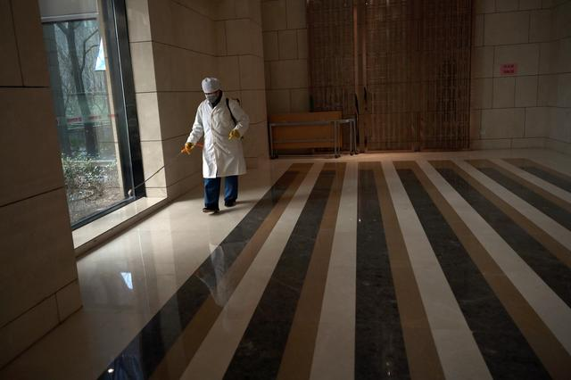 Worker Wang Fu wearing a face mask sprays disinfectant at an apartment's lobby in a residential compound, as the country is hit by an outbreak of the novel coronavirus, in Beijing, China February 21, 2020. REUTERS/Tingshu Wang