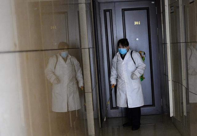 Worker Gong Lixia wearing a face mask sprays disinfectant to sanitize an apartment building at a residential compound, as the country is hit by an outbreak of the novel coronavirus, in Beijing, China February 21, 2020. REUTERS/Tingshu Wang