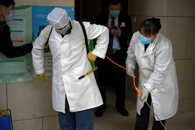 Worker Gong Lixia helps her colleague Wang Fu to put on the disinfectant liquid backpack as they sanitise a residential compound, following an outbreak of the novel coronavirus in the country, in Beijing, China February 21, 2020. REUTERS/Tingshu Wang