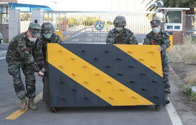 South Korean marines place a barricade after a sailor of the unit was confirmed to have been infected with coronavirus at Navy unit in Jeju Island, South Korea, February 21, 2020.  Yonhap/Handout via REUTERS