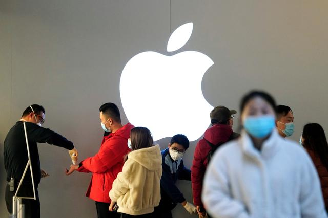 People wearing protective masks wait for checking their temperature in an Apple Store, in Shanghai, China, as the country is hit by an outbreak of the novel coronavirus, February 21, 2020. REUTERS/Aly Song