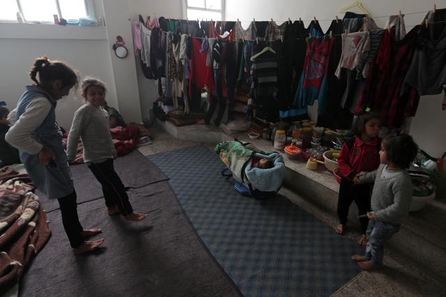 Internally displaced children stand near hanging clothes inside a room at an empty school and university compound used as shelter, in Azaz, Syria February 21, 2020.  REUTERS/Khalil Ashawi