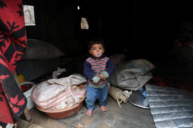 An internally displaced child looks out from a tent, erected at an empty school and university compound used as shelter in Azaz, Syria February 21, 2020.  REUTERS/Khalil Ashawi